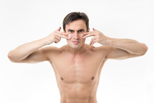 Middelgrote geschotene mens die gezichtslotion toepassen