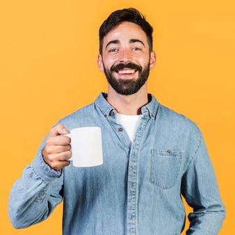 Middelgrote geschotene smiley kerel die een kop houdt