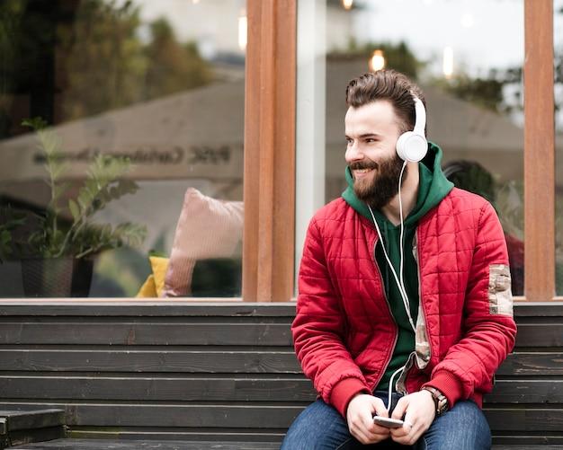 Middelgrote geschotene smileykerel met hoofdtelefoons die op een bank zitten