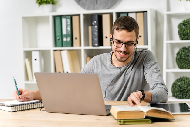 Middelgrote geschotene smileystudent die met laptop bestudeert