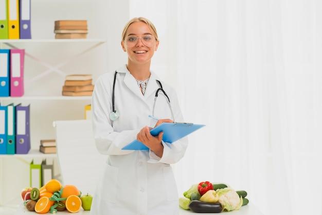 Middelgrote geschotene smileyvoedingsdeskundige met stethoscoop