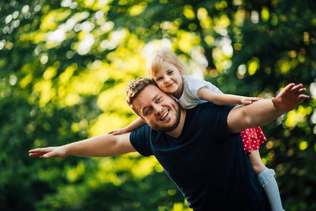 Middelgrote geschotene vader en dochter die bij camera glimlachen