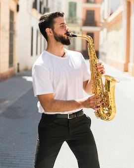 Middelgrote geschotene vooraanzichtmusicus het spelen saxofoon in straat