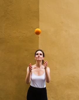 Middelgrote geschotene vrouw die een sinaasappel werpt