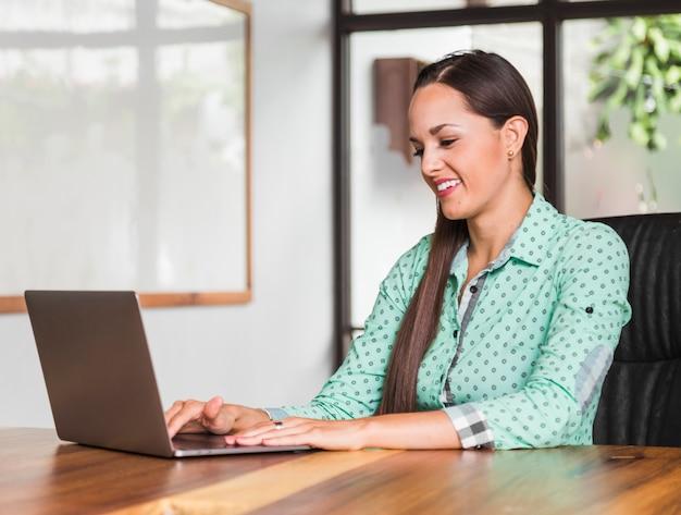 Middelgrote geschotene vrouw die op haar laptop kijkt