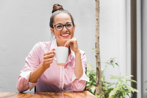 Middelgrote geschotene vrouw met glazen op het kantoor