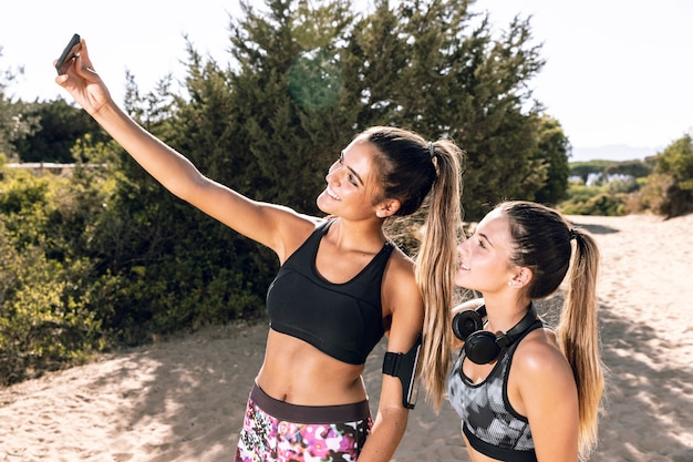 Middelgrote geschotene vrouwen bij het aanstoten die een selfie nemen
