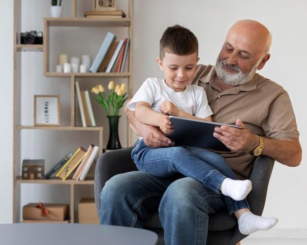 Middelgrote grootvader met kind en tablet
