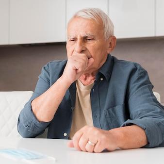 Middelgrote hoestende oude man