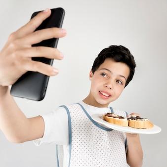 Middelgrote jongen die selfies maakt