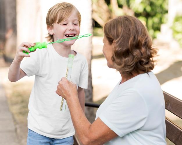 Middelgrote jongen die zeepballonnen maakt