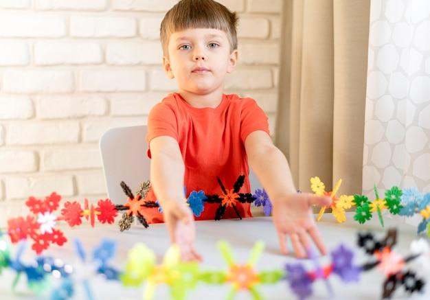 Middelgrote jongen met bloemen speelgoed