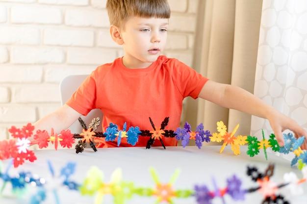 Middelgrote jongen met bloemenspeelgoed