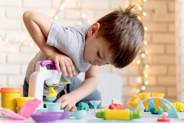 Middelgrote jongen met speelgoed