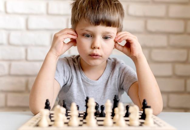 Middelgrote jongen schaken
