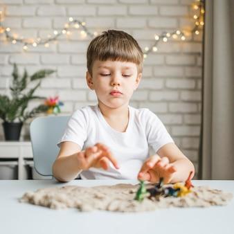 Middelgrote jongen spelen met dinosaurus