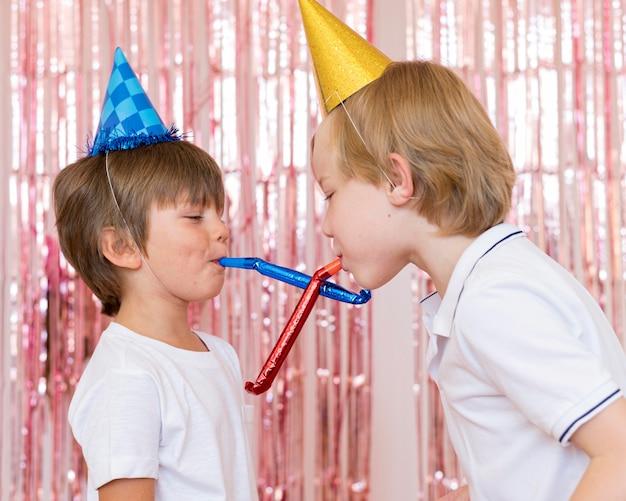 Middelgrote jongens die met fluitjes spelen