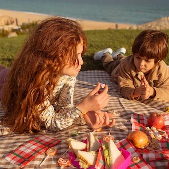 Middelgrote kinderen die buiten eten