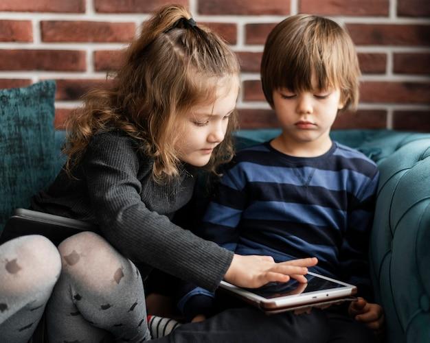 Middelgrote kinderen die op de bank zitten
