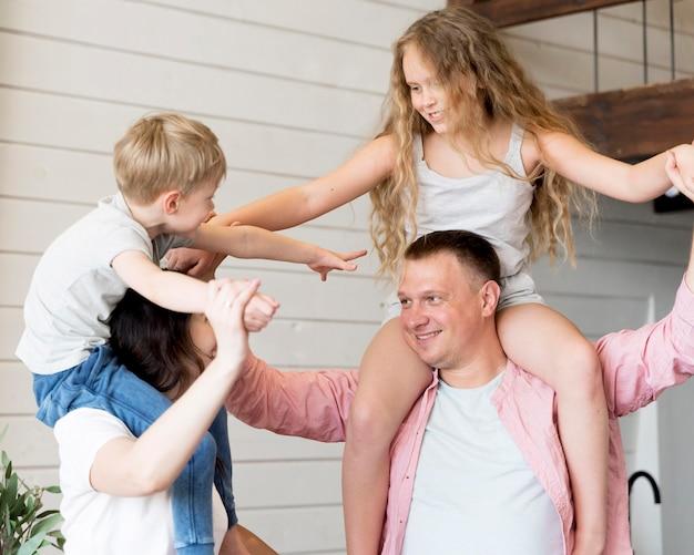 Middelgrote kinderen en ouders die plezier hebben