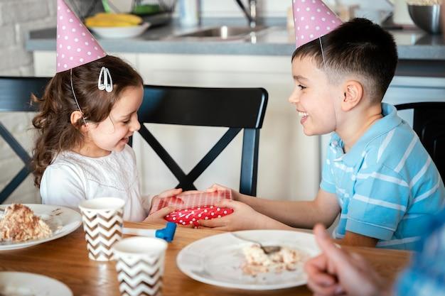 Middelgrote kinderen met feestmutsen