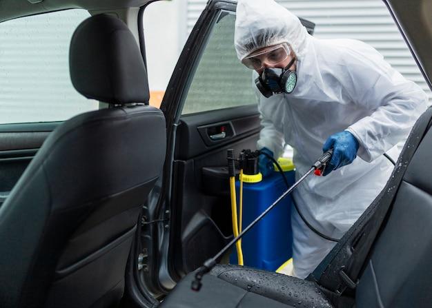 Middelgrote man die auto desinfecteert