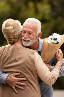 Middelgrote man die bloemen aanbiedt aan vrouw