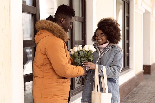Middelgrote man die bloemen aanbiedt