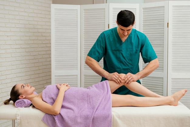Middelgrote man die knie masseert