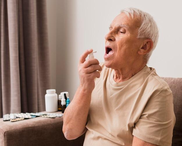 Middelgrote man die orale spray gebruikt