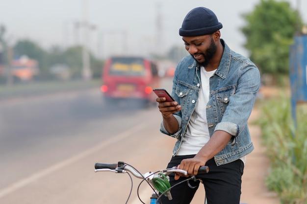 Middelgrote man met fiets en telefoon
