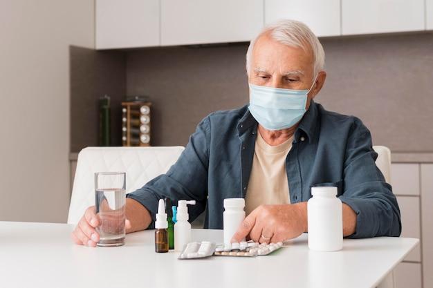 Middelgrote man met masker en medicijn