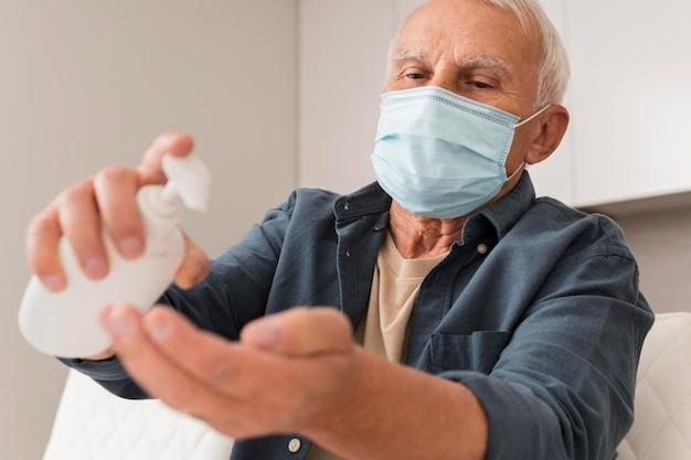 Middelgrote man met masker en ontsmettingsmiddel