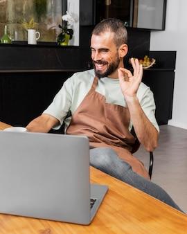 Middelgrote man zittend aan tafel met schort