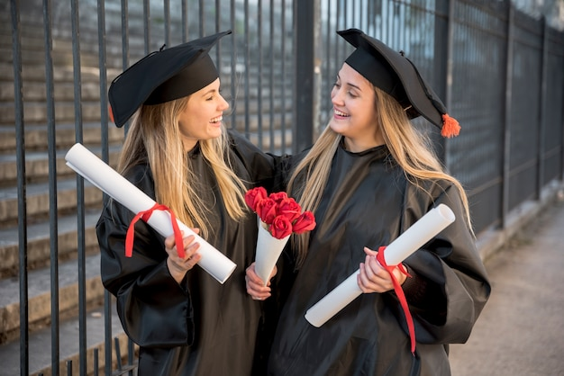 Middelgrote meningsvrienden met boeket van rozen bij graduatie
