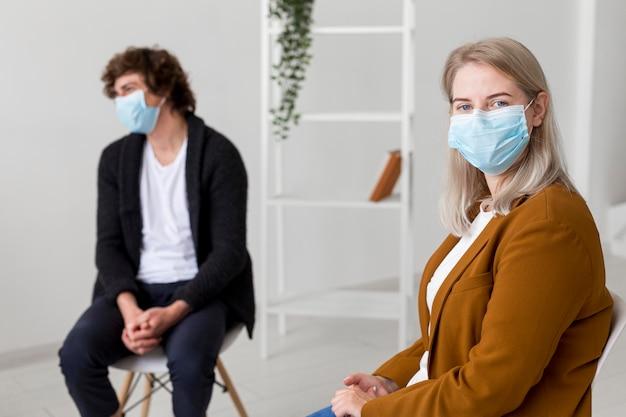 Middelgrote mensen die binnenshuis maskers dragen