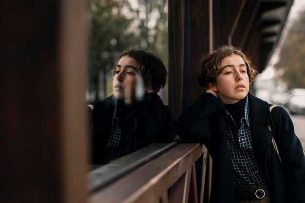 Middelgrote niet-binaire persoon die naast het raam staat