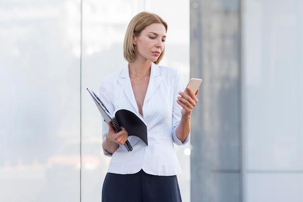 Middelgrote ondernemer die telefoon controleert