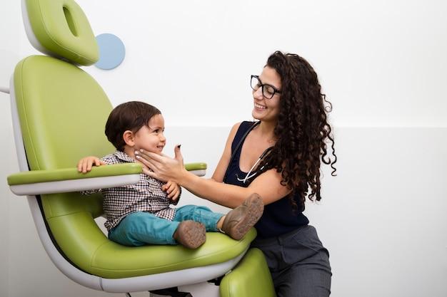 Middelgrote ontsproten arts die een babyjongen onderzoekt