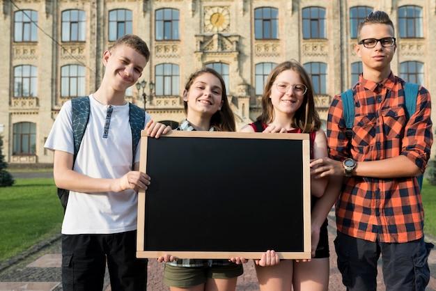 Middelgrote ontsproten tieners die bord houden