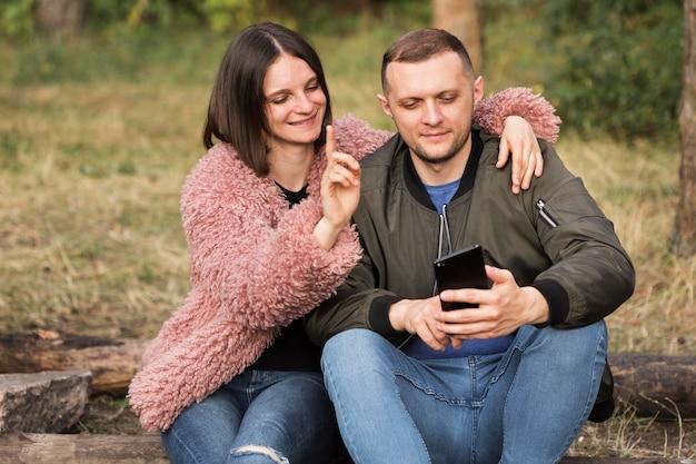 Middelgrote partners die naar telefoon kijken