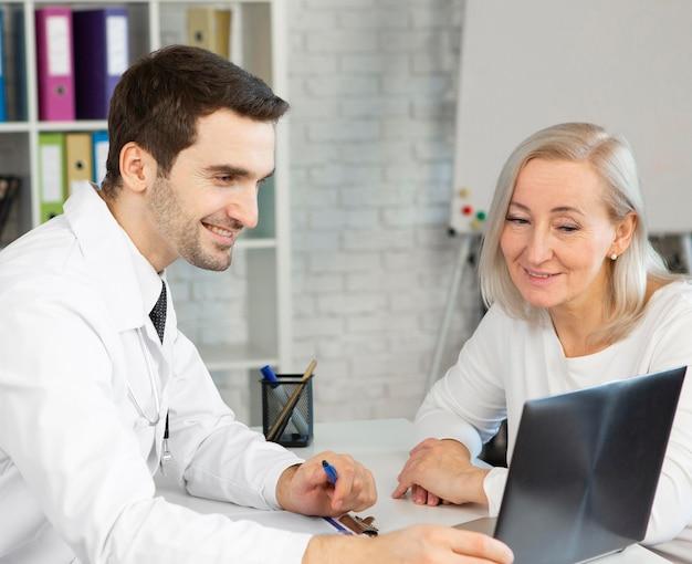 Middelgrote patiënt die naar radiografie kijkt