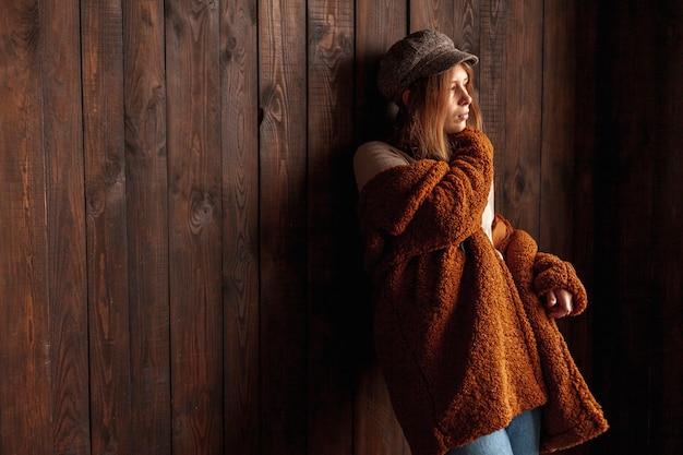 Middelgrote schotvrouw met het houten stellen als achtergrond