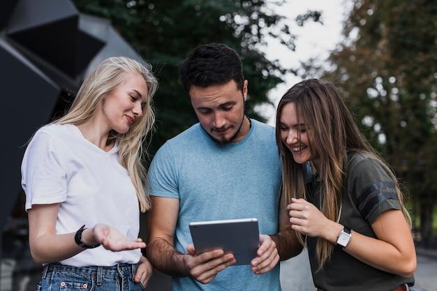 Middelgrote shot lachende tieners die in een tablet kijken