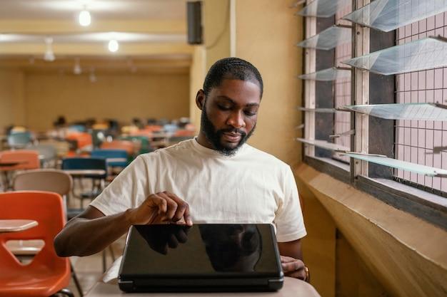 Middelgrote student die laptop opent