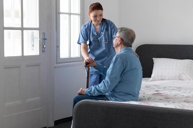 Middelgrote verpleegster die de man controleert