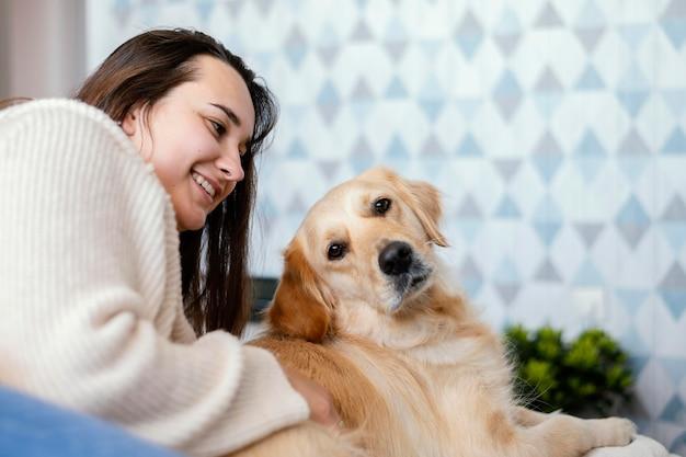 Middelgrote vrouw die hond aait