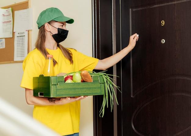 Middelgrote vrouw die op de deur klopt