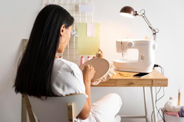 Middelgrote vrouw die thuis naait