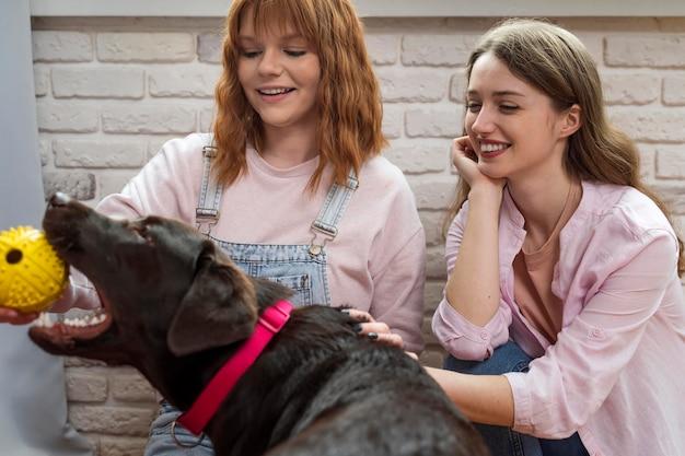Middelgrote vrouwen die met hond spelen